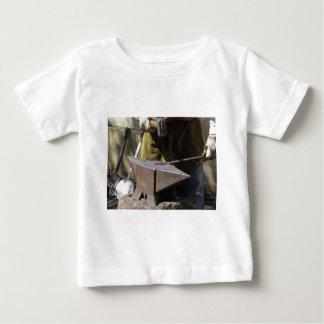 Blacksmith manually forging the molten metal baby T-Shirt