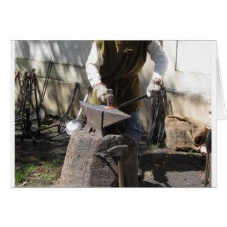 Blacksmith manually forging the molten metal card