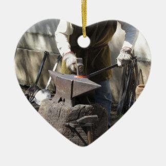 Blacksmith manually forging the molten metal ceramic heart ornament
