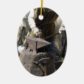 Blacksmith manually forging the molten metal ceramic oval ornament