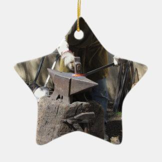 Blacksmith manually forging the molten metal ceramic star ornament