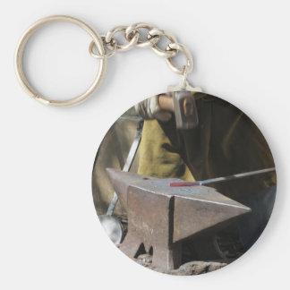 Blacksmith manually forging the molten metal keychain