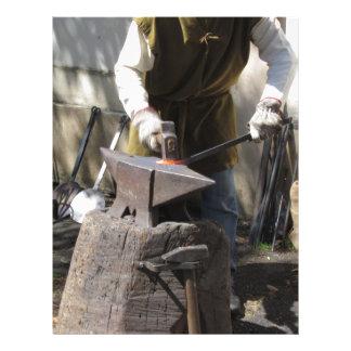 Blacksmith manually forging the molten metal letterhead