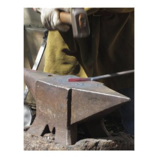 Blacksmith manually forging the molten metal letterhead