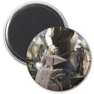 Blacksmith manually forging the molten metal magnet