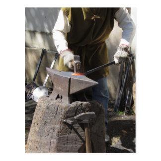 Blacksmith manually forging the molten metal postcard