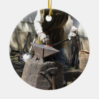 Blacksmith manually forging the molten metal round ceramic ornament