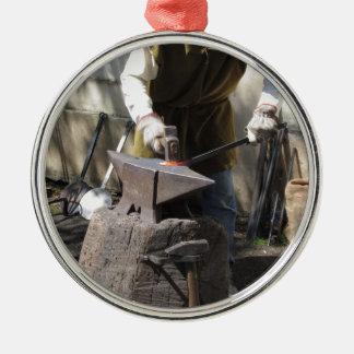 Blacksmith manually forging the molten metal Silver-Colored round ornament
