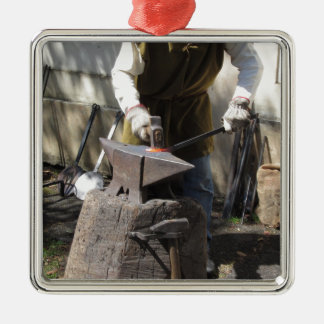 Blacksmith manually forging the molten metal Silver-Colored square ornament