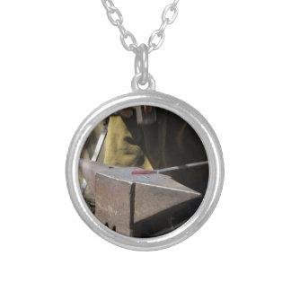 Blacksmith manually forging the molten metal silver plated necklace