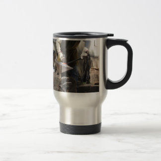 Blacksmith manually forging the molten metal travel mug