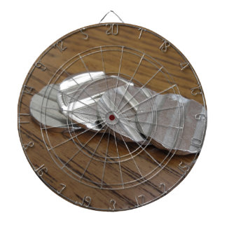 Blank metallic coins on wooden table dart board