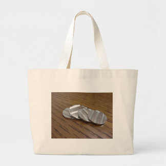 Blank metallic coins on wooden table large tote bag