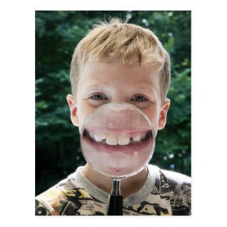 blond boy behind magnifying glass smiling postcard