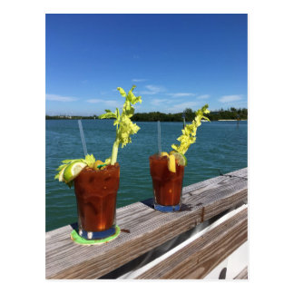Bloody Mary drinks on a railing with ocean Postcard