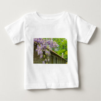 Blooming blue wisteria hanging over long brick wal baby T-Shirt
