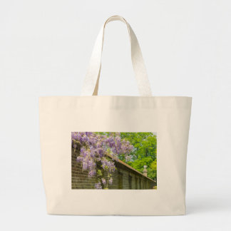 Blooming blue wisteria hanging over long brick wal large tote bag