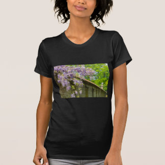 Blooming blue wisteria hanging over long brick wal T-Shirt