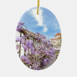 Blooming blue Wisteria sinensis on fence in Greece Ceramic Oval Ornament