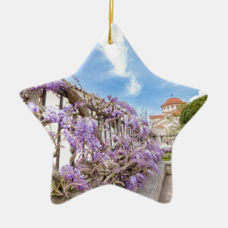 Blooming blue Wisteria sinensis on fence in Greece Ceramic Star Ornament
