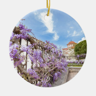 Blooming blue Wisteria sinensis on fence in Greece Round Ceramic Ornament