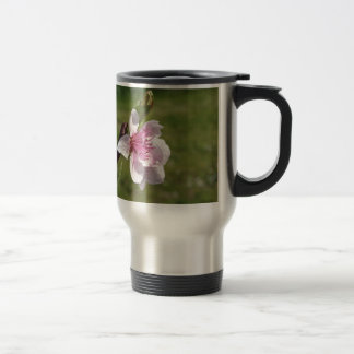 Blossoming peach tree against the green garden travel mug