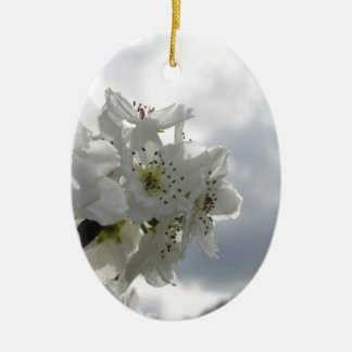 Blossoming pear tree against the cloudy sky ceramic ornament