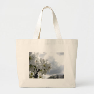 Blossoming pear tree against the cloudy sky large tote bag