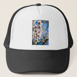 Blossoming tree branch with white flowers trucker hat