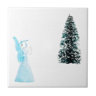 Blue glass angel praying near christmas tree tile