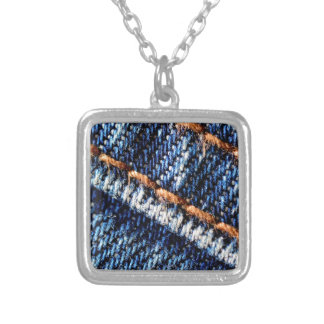 Blue jeans closeup texture. silver plated necklace