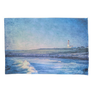 Blue lighthouse in evening and ocean waves pillowcase