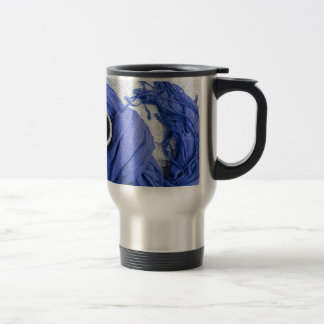 Blue scarf tied around the mug with hot coffee