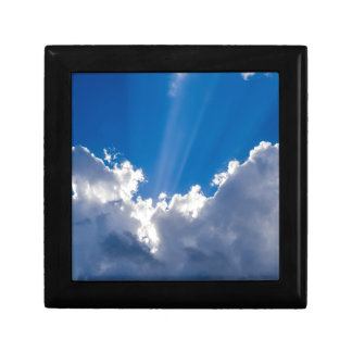 Blue sky with white clouds and ray of sunshine. gift box