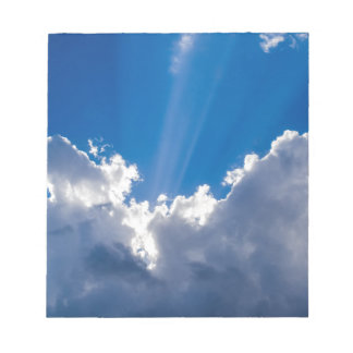 Blue sky with white clouds and ray of sunshine. notepad