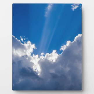 Blue sky with white clouds and ray of sunshine. plaque