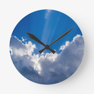 Blue sky with white clouds and ray of sunshine. round clock