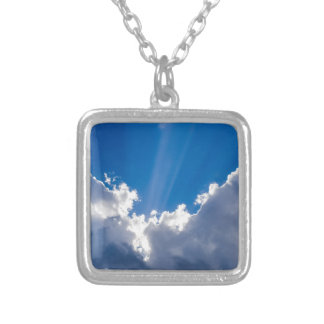 Blue sky with white clouds and ray of sunshine. silver plated necklace