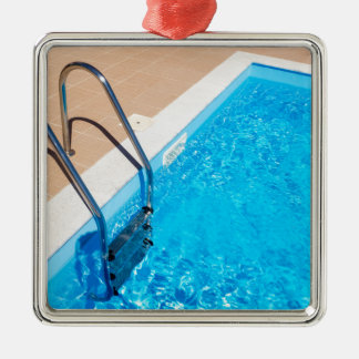 Blue swimming pool with ladder metal ornament