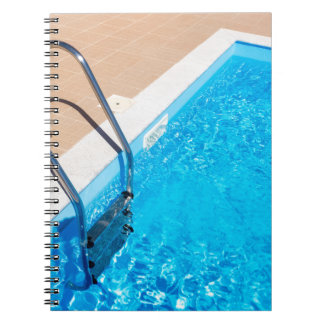 Blue swimming pool with ladder notebooks