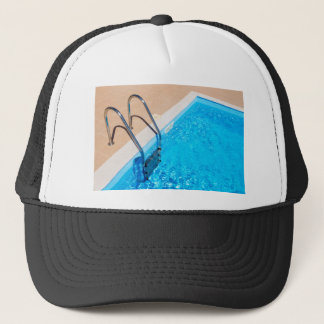 Blue swimming pool with ladder trucker hat