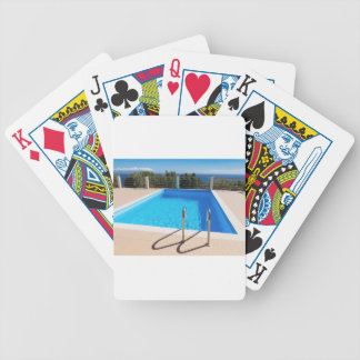 Blue swimming pool with steps at sea bicycle playing cards