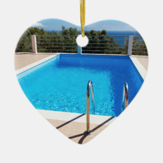 Blue swimming pool with steps at sea ceramic heart ornament
