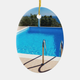 Blue swimming pool with steps at sea ceramic oval ornament
