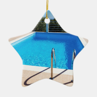 Blue swimming pool with steps at sea ceramic star ornament