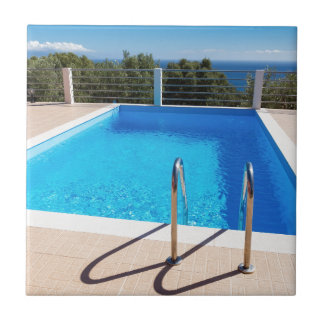 Blue swimming pool with steps at sea ceramic tiles