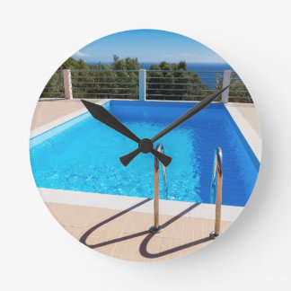 Blue swimming pool with steps at sea clocks