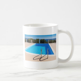 Blue swimming pool with steps at sea coffee mug