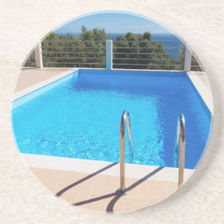 Blue swimming pool with steps at sea drink coaster
