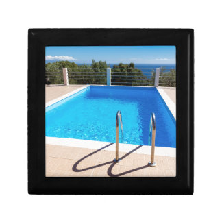 Blue swimming pool with steps at sea gift box
